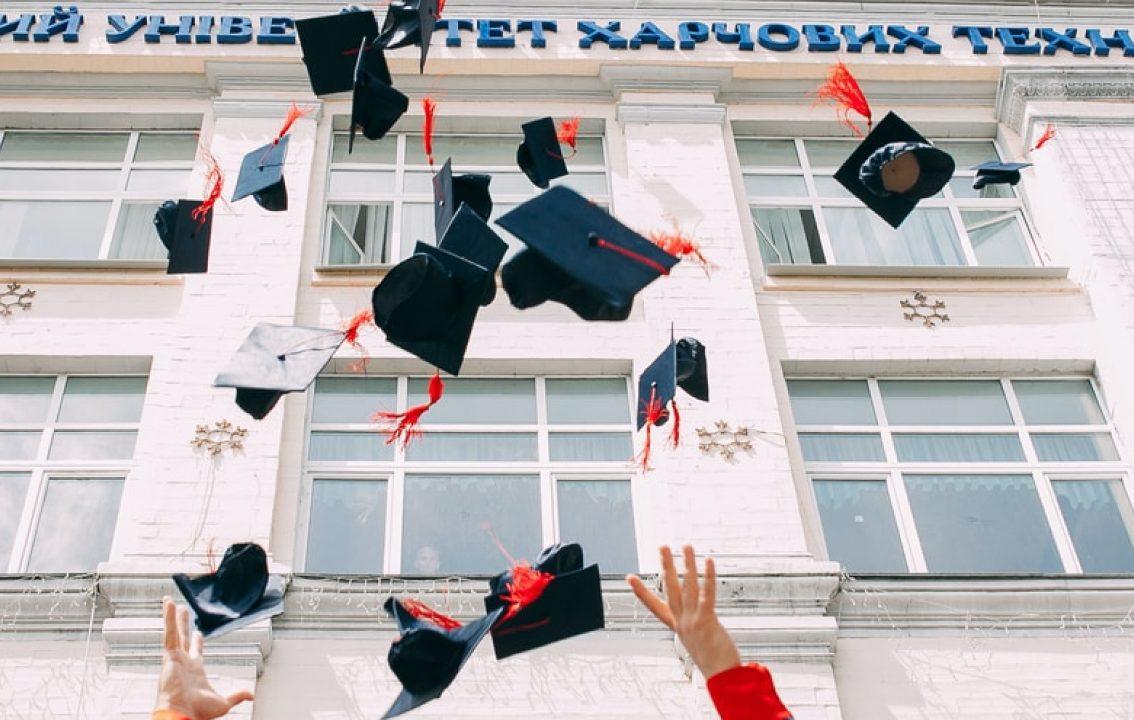 Graduates throwing graduation caps in air.